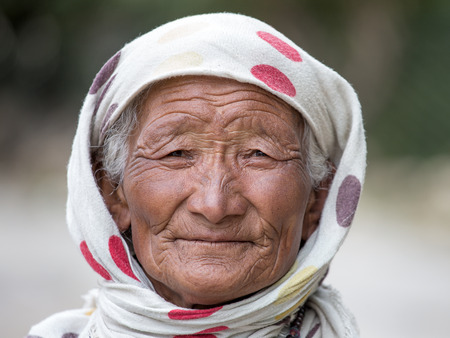the descendant: LEH IN LADAKH, INDIA - SEPTEMBER 03 2014: Old unidentified local woman sitting outdoor in Leh. The majority of the local population are descendant of Tibetan. Editorial