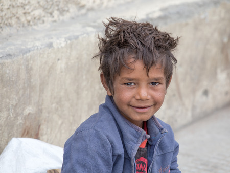 squalor: LEH, INDIA - SEPTEMBER 08 2014: An unidentified beggar boy begs for money from a passerby in Leh. Poverty is a major issue in India