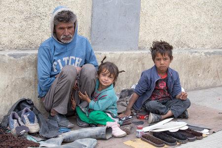 LEH, INDIA - 08 de septiembre 2014: Una familia mendigo no identificado pide dinero a un transeúnte en Leh. La pobreza es un problema importante en la India
