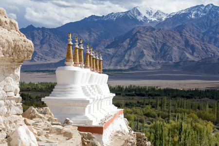 Buddhist chortens (stupa) and Himalayas mountains in the background near Shey Palace in Ladakh, India