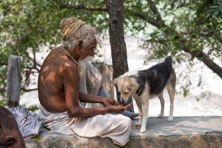 hombre pobre: Rishikesh, India - 05 de octubre 2014: pobre hombre no identificado y el perro se sienta en el ghat en el r�o Ganges. Indios pobres acuden a Rishikesh para la caridad. Editorial
