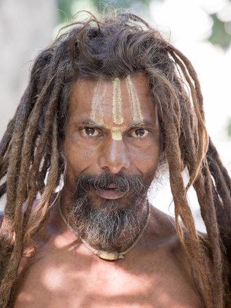 underprivileged: RISHIKESH, INDIA - 11 ottobre 2014: Unidentified povero uomo si siede sul ghat lungo il fiume Gange. Poveri indiani affollano Rishikesh per beneficenza.