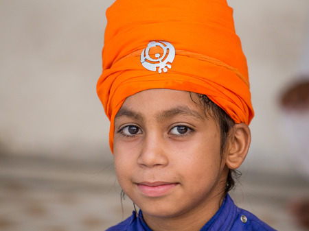 sikh: AMRITSAR, INDIA - SEPTEMBER 27, 2014: Unidentified young Sikh boy visiting the Golden Temple in Amritsar, Punjab, India. Sikh pilgrims travel from all over India to pray at this holy site.