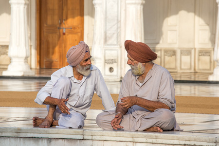 sikhism: AMRITSAR, INDIA - SEPTEMBER 27, 2014: Unidentified Sikh men visiting the Golden Temple in Amritsar, Punjab, India. Sikh pilgrims travel from all over India to pray at this holy site. Editorial
