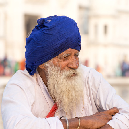 stocky: AMRITSAR, INDIA - SEPTEMBER 27, 2014: Unidentified Sikh man visiting the Golden Temple in Amritsar, Punjab, India. Sikh pilgrims travel from all over India to pray at this holy site.