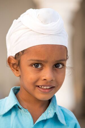 punjab: AMRITSAR, INDIA - SEPTEMBER 27, 2014: Unidentified young Sikh boy visiting the Golden Temple in Amritsar, Punjab, India. Sikh pilgrims travel from all over India to pray at this holy site.