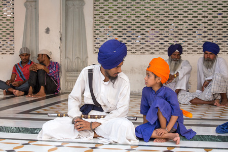 stocky: AMRITSAR, INDIA - SEPTEMBER 27, 2014: Unidentified Sikh man and boy visiting the Golden Temple in Amritsar, Punjab, India. Sikh pilgrims travel from all over India to pray at this holy site.