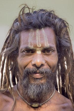 hombre pobre: Rishikesh, India - 11 de octubre 2014: el hombre no identificado pobre se sienta en el ghat en el r�o Ganges. Indios pobres acuden a Rishikesh para la caridad.