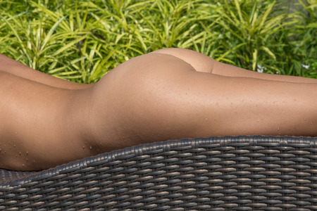 nude: Girl sunbathes nude in a tropical garden