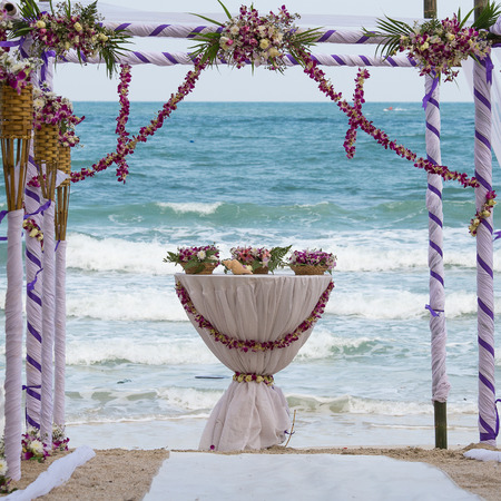 cabana: wedding arch decorated with flowers on tropical sand beach, outdoor beach wedding setup