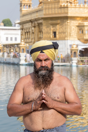 amritsar: AMRITSAR, INDIA - SEPTEMBER 29, 2014: Unidentified Sikh man visiting the Golden Temple in Amritsar, Punjab, India. Sikh pilgrims travel from all over India to pray at this holy site.