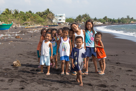 mayon: LEGAZPI, PHILIPPINES - MARCH 18, 2014: Unidentified poor but healthy children group portrait on the beach with volcanic sand near Mayon volcano