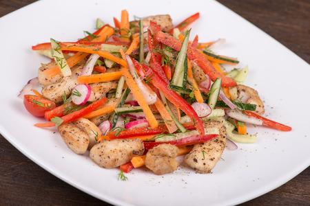 ensalada de verduras: Ensalada de verduras frescas con carne de pollo en un plato blanco Foto de archivo