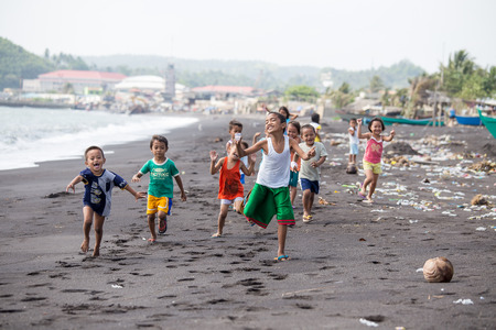 filipino people: LEGAZPI, PHILIPPINES - MARCH 18, 2014: Unidentified poor but healthy children group on the beach with volcanic sand near Mayon volcano