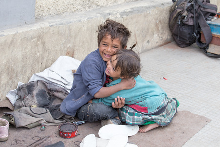 begs: LEH, INDIA - SEPTEMBER 08 2014: An unidentified beggar girl and boy begs for money from a passerby in Leh. Poverty is a major issue in India