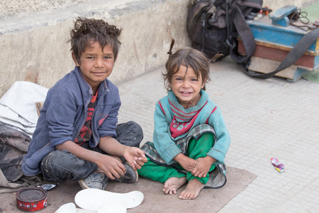 LEH, INDIA - SEPTEMBER 08 2014: An unidentified beggar girl and boy begs for money from a passerby in Leh. Poverty is a major issue in India