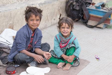 crisis economica: LEH, INDIA - 08 de septiembre 2014: Una mendiga no identificado y el niño pide limosna de un transeúnte en Leh. La pobreza es un problema importante en la India
