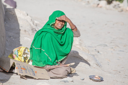 begs: LEH, INDIA - SEPTEMBER 08 2014: An unidentified poor woman begs for money from a passerby in Leh. Poverty is a major issue in India