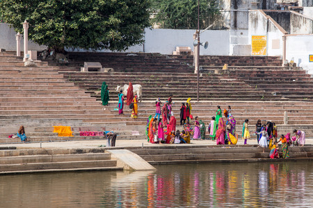PUSHKAR, INDIA - OCTOBER 27, 2014: Unidentified people perform puja - ritual ceremony at holy Sarovar lake. Pushkar - famous worship place in India