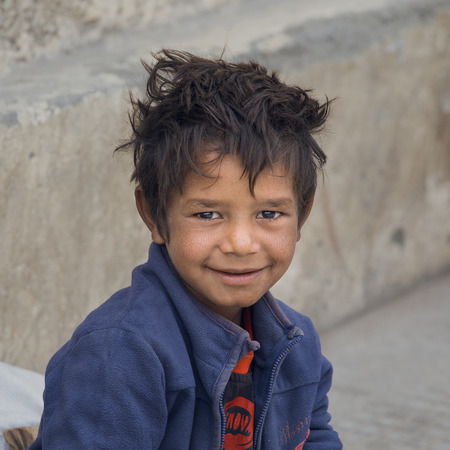 begs: LEH, INDIA - SEPTEMBER 08 2014: An unidentified beggar boy begs for money from a passerby in Leh. Poverty is a major issue in India