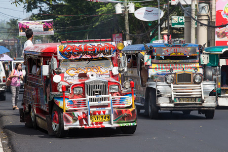 LEGAZPI, PHILIPPINES - MARCH 18: Jeepneys passing, Filipino inexpensive bus service. Jeepneys are the most popular means of public transportation in the Philippines. 에디토리얼
