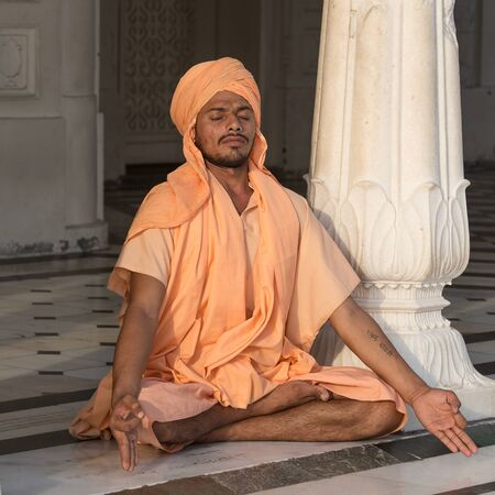 amritsar: AMRITSAR, INDIA - SEPTEMBER 27, 2014: Unidentified Indian man meditates in the Golden Temple in Amritsar, Punjab, India. Sikh pilgrims travel from all over India to pray at this holy site. Editorial