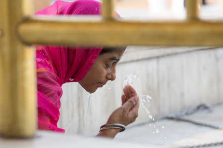 amritsar: AMRITSAR, INDIA - SEPTEMBER 27, 2014: Unknown indian girl visiting the Golden Temple in Amritsar, Punjab, India. Sikh pilgrims travel from all over India to pray at this holy site.