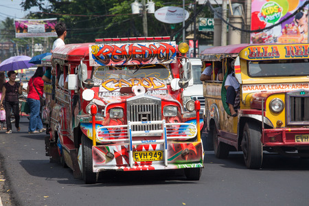 LEGAZPI, PHILIPPINES - MARCH 18, 2014: Jeepneys passing, Filipino inexpensive bus service. Jeepneys are the most popular means of public transportation in the Philippines. 에디토리얼