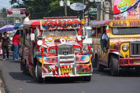 LEGAZPI, Filippijnen - 18 maart 2014: Jeepneys passeren, Filippijnse goedkope busdienst. Jeepneys zijn de meest populaire vormen van openbaar vervoer in de Filippijnen.