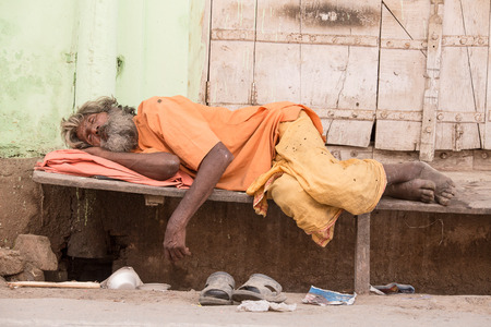 underdeveloped: PUSHKAR, INDIA - OCTOBER 24, 2014: Unidentified Indian homeless man sleeps  near the ghat along the sacred Sarovar lake. Poor Indians flock to Pushkar for charity. Editorial