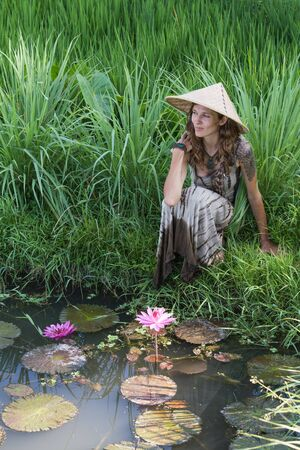 indonesia girl: Portrait of a girl in a straw hat near the lake with lilies and paddy field in Bali, Indonesia Stock Photo