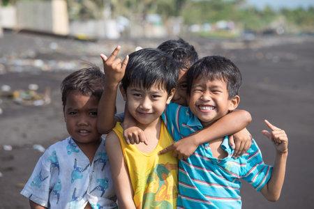 POBRES NI�OS: LEGAZPI, Filipinas - 18 de marzo 2014: no identificados a los ni�os pobres pero sanos retrato de grupo en la playa con arena volc�nica cerca del volc�n Mayon