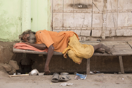 PUSHKAR, INDIA - OCTOBER 24, 2014: Unidentified Indian homeless man sleeps  near the ghat along the sacred Sarovar lake. Poor Indians flock to Pushkar for charity. Editorial