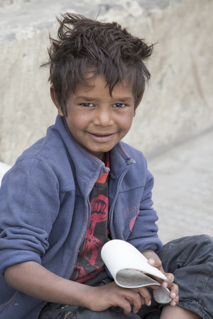 begs: LEH, INDIA - SEPTEMBER 08, 2014: An unidentified beggar boy begs for money from a passerby in Leh. Poverty is a major issue in India