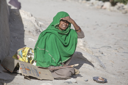 begs: LEH, INDIA - SEPTEMBER 08, 2014: An unidentified poor woman begs for money from a passerby in Leh. Poverty is a major issue in India