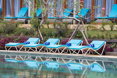 lounge chairs: Relaxing lounge chairs by the swimming pool