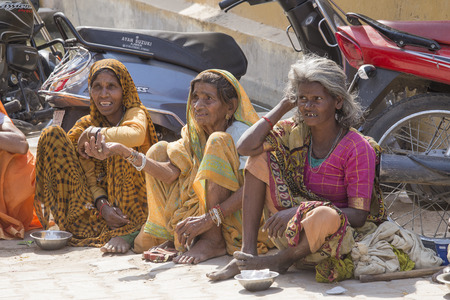 destitute: PUSHKAR, INDIA - OCTOBER 28, 2014:Unknown old indian beggars waits for alms on a street on the along ghat the sacred Sarovar lake. Pushkar - famous worship place in India