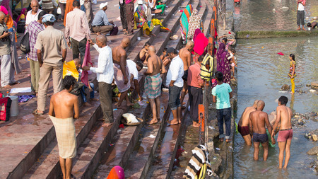 HARIDWAR, INDIA - OCTOBER 21, 2014: Unidentified Indian people at ritual washing in the sacred Ganges river. Haridwar - famous worship place in India