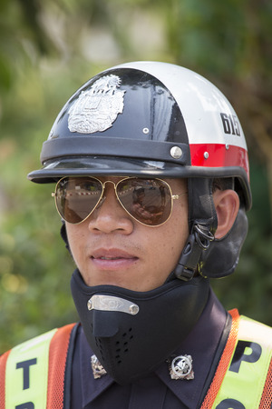 warning vest: PAI, THAILAND - APRIL 11, 2015 : Unidentified traffic police officer works on a busy road. Police regularly direct traffic in busy areas. Editorial