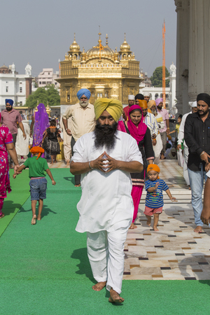 amritsar: AMRITSAR, INDIA - SEPTEMBER 28, 2014: Unidentified Sikhs and indian people visiting the Golden Temple in Amritsar, Punjab, India. Sikh pilgrims travel from all over India to pray at this holy site.