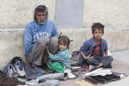 begs: LEH, INDIA - SEPTEMBER 08, 2014: An unidentified beggar family begs for money from a passerby in Leh. Poverty is a major issue in India Editorial