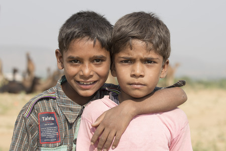 arab beast: PUSHKAR, INDIA - OCTOBER 26, 2014:Unknown two young boy and camel involved in Pushkar Camel Mela , Pushkar Camel Fair . This fair is the largest camel trading fair in the world.