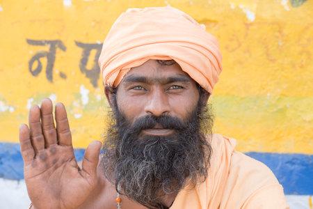 sadhu: PUSHKAR, INDIA - OCTOBER 24, 2014: Unidentified Indian sadhu - holy man, sits on the ghat along the sacred Sarovar lake. Pushkar - famous worship place in India
