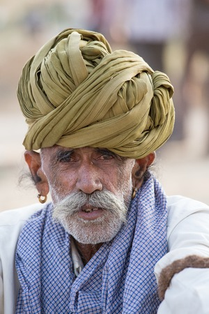 herder: PUSHKAR, INDIA - OCTOBER 28, 2014: Unidentified Indian man attended the annual Pushkar Camel Mela. This fair is the largest camel trading fair in the world.