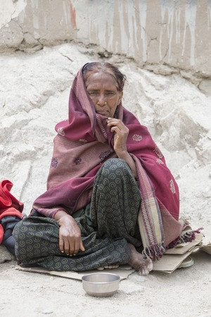 unfortunate: LEH, INDIA - JUNE 24, 2015: Unknown poor woman begs for money from a passerby on the street in Leh, Ladakh. Poverty is a major issue in India