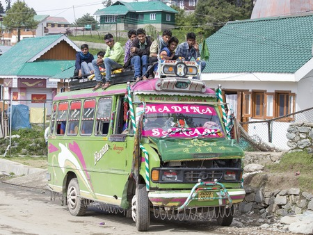 inexpensive: SRINAGAR, INDIA - JUNE 07, 2015: Local bus in indian inexpensive bus service. Local residents ride on the roof of the bus