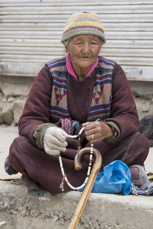 poverty india: LEH, INDIA - JUNE 21, 2015: Unidentified beggar woman on the street in Leh, Ladakh. Poverty is a major issue in India