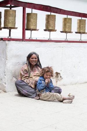 underprivileged: LEH, INDIA - 24 Giugno 2015: Sconosciuta donna mendicante con un bambino accattonaggio nei pressi di un tempio buddista a Leh, Ladakh. La povert� � un problema importante in India