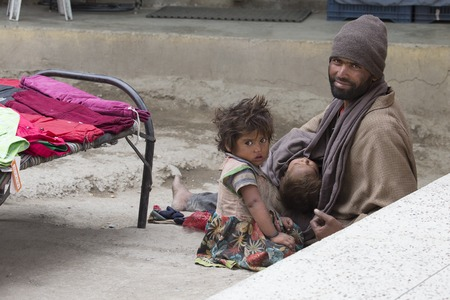underprivileged: LEH, INDIA - JUNE 24, 2015: Unknown beggar man with children begging on the street in Leh, Ladakh. Poverty is a major issue in India