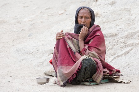 LEH, INDIA - JUNE 24, 2015: Unknown poor woman begs for money from a passerby on the street in Leh, Ladakh. Poverty is a major issue in India